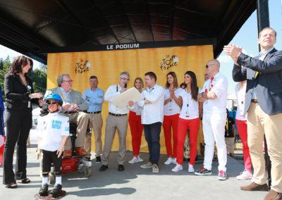 Sous les yeux de Muriel Targnion, bourgmestre de Verviers, Christophe Penot, l'organisateur, présente au lauréat, Stéphane Thirion, le portfolio du 13<sup>e</sup> Prix Jacques-Goddet frappé aux couleurs du Tour de France et de Carrefour. Une autre façon de saluer tous ceux qui concourent, d'année en année, au rayonnement du Prix Jacques-Goddet.
