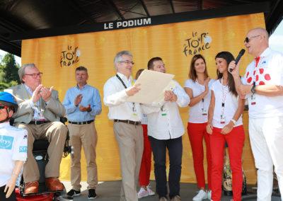 Éric Marchyllie au micro. Responsable sponsoring de Carrefour France, il veut à la fois saluer un ami et un reporter qui restera dans la mémoire du Prix Jacques-Goddet.