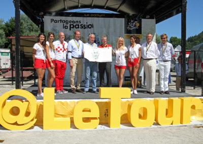 Photographie officielle de la remise du 12<sup>e</sup> Prix Jacques-Goddet à Moirans-en-Montagne, sous les couleurs habituelles du maillot blanc à pois rouges. François Thomazeau, le lauréat, a reçu son trophée des mains de Christian Prudhomme, le directeur du Tour de France, accompagné d'Éric Marchyllie, responsable sponsoring de Carrefour France, et Frédéric Ebling, directeur des affaires publiques du groupe Carrefour France.