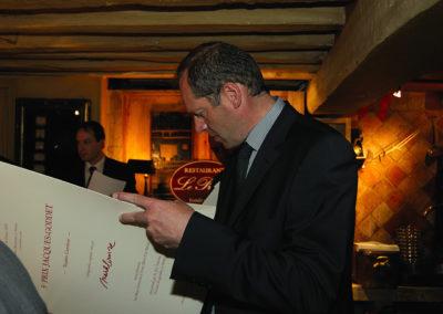 Un lecteur attentif. Christian Prudhomme découvre l'œuvre spécialement réalisée par <a href=https://www.prix-jacques-goddet.com/les-artistes>Mark Brusse</a> pour le 5<sup>e</sup> Prix Jacques-Goddet ainsi que le texte consacré à l'artiste néerlandais.