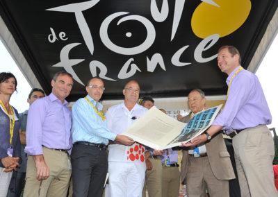 Éric Marchyllie, responsable sponsoring de Carrefour France, a remis à Jean-François Quénet le portfolio du 7<sup>e</sup> Prix Jacques-Goddet en compagnie de Michel Rocard et de Christian Prudhomme. Bernard Hinault, le quintuple vainqueur du Tour de France, à gauche, leur a fait l'amitié de leur prêter main forte !