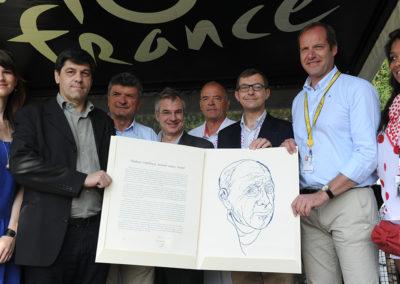 La découverte du portfolio réservé au lauréat. Jean-Luc Gatellier l'a reçu des mains de Christian Prudhomme et de Frédéric Ebling, sous le regard complice de sa fille Lucie (en bleu) et de Bernard Thévenet.
