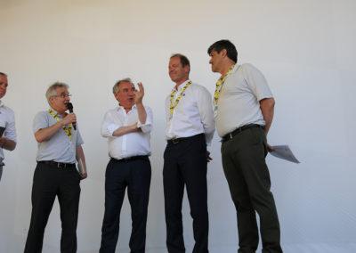 Remise du 15<sup>e</sup> Prix Jacques-Goddet sur le podium du Village du Tour, à Pau, le 19 juillet 2019, cent ans jour pour jour après la création du maillot jaune. Au nom d'Edeis l'Allié des territoire, partenaire du Prix, Christophe Penot ouvre la cérémonie, tandis que François Bayrou, maire de la ville, salue déjà Jean-Luc Gatellier, premier journaliste à inscrire deux fois son nom au palmarès.